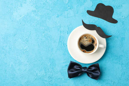Cup of coffee, bow tie, decorative mustache and hat on blue background, space for text and top view