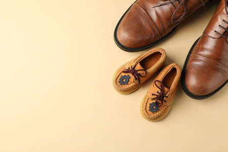 Brown leather shoes and children's shoes on color background, space for text and top view Фото со стока