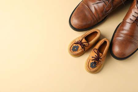 Zapatos de cuero marrón y zapatos para niños sobre fondo de color, espacio para texto y vista superior Foto de archivo