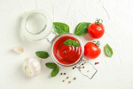 Flache Zusammensetzung mit frischen Tomaten, Basilikum, Pfeffer, Knoblauch und Sauce im Glas auf weißem Hintergrund, Platz für Text und Draufsicht