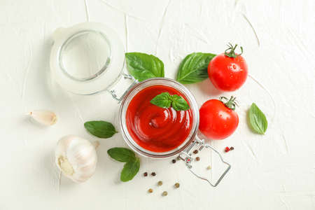 Flat lay composition with fresh tomatoes, basil, pepper, garlic and sauce in glass jar on white background, space for text and top view