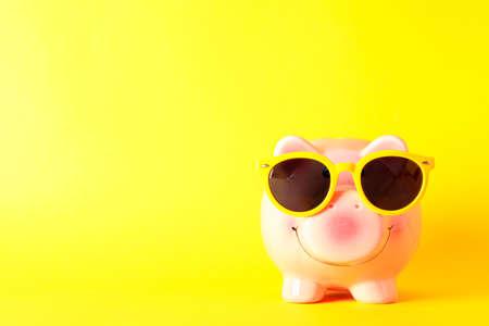 Glückliches Sparschwein mit Sonnenbrille auf gelbem Hintergrund, Platz für Text. Finanzieren, Geld sparen Standard-Bild