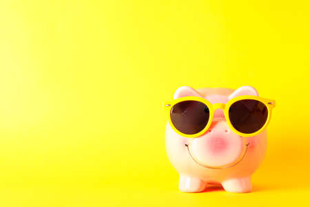 Happy piggy bank with sunglasses on yellow background, space for text. Finance, saving money
