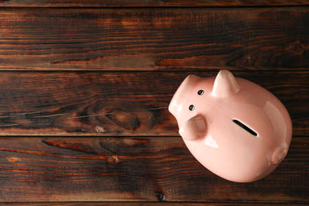 Happy piggy bank on wooden background, space for text and top view. Finance, saving money Imagens