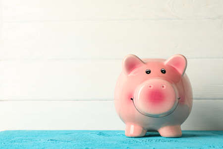 Happy piggy bank on color table against white wooden background, space for text. Finance, saving money