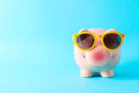 Happy piggy bank with sunglasses on color background, space for text. Finance, saving money
