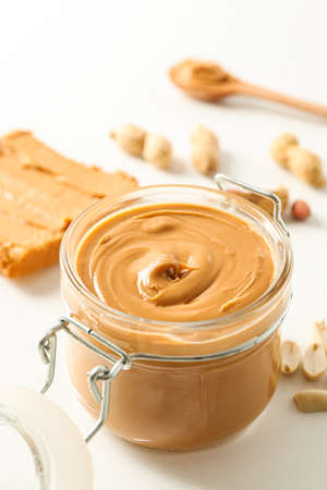 Composition with peanut butter sandwich, glass jar, peanut and spoon on white background, space for text and closeup