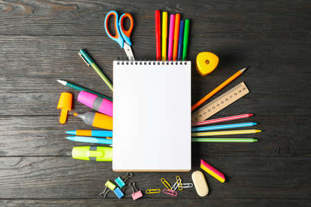 Flat lay composition with school supplies on wooden background, space for text 写真素材