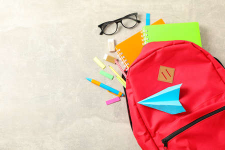 Flat lay composition with backpack and school supplies on grey background