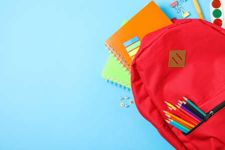 Flat lay composition with backpack and school supplies on color background