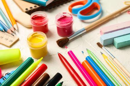 School supplies on white wooden background, closeup