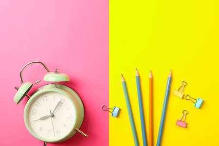 Composition with alarm clock, pencils and clips on two tone background, space for text Stockfoto