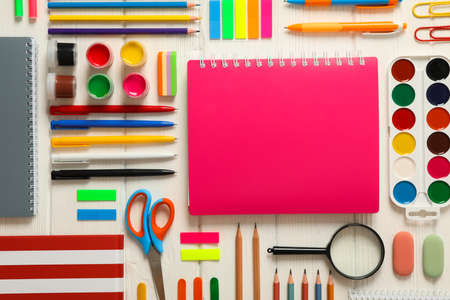 Flat lay composition with school supplies on white wooden background