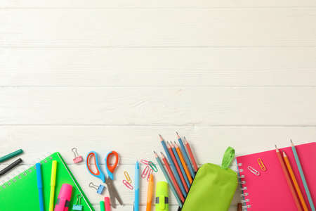 Flat lay composition with school supplies on white wooden background, space for text Stockfoto