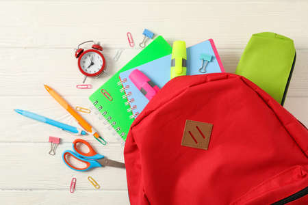 Flat lay composition with backpack and school supplies on white wooden background