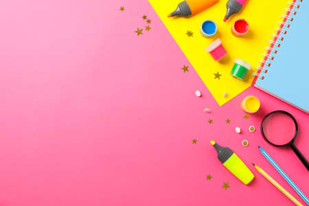 Flat lay composition with school supplies on two tone background, space for text