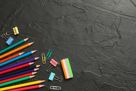Composition with school supplies on black background, space for text
