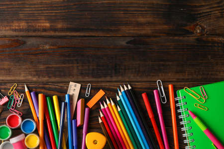 Flat lay composition with school supplies on wooden background, space for text Stockfoto