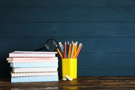 Composition with school supplies on wood table against dark background