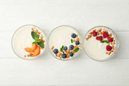 Flat lay composition with yogurt desserts and ingredients on white wooden background