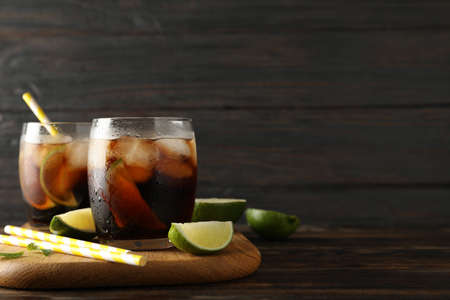 Glasses with ice cola, lime slices and tubules on wooden background
