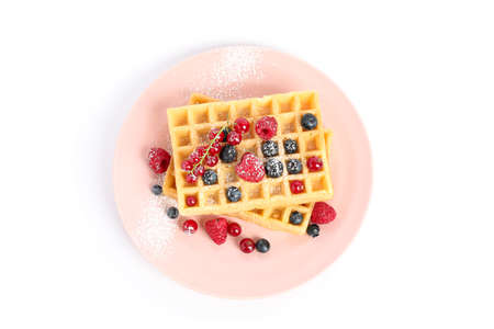 Belgian waffles with berries on plate isolated on white background