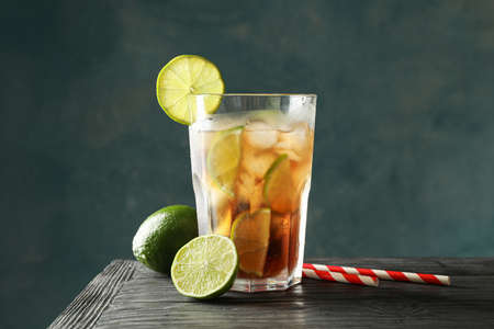 Glass of cold cola with citrus and ice on wooden table against dark background