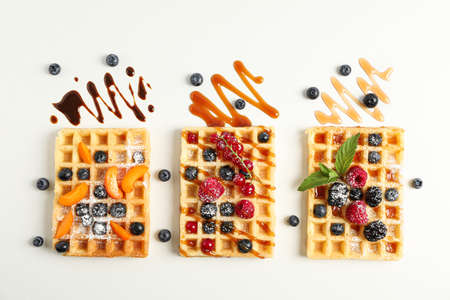 Flat lay composition with belgian waffles and different toppings, top view Standard-Bild