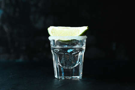 Tequila shot with lime and salt against black background with blue light Stock Photo