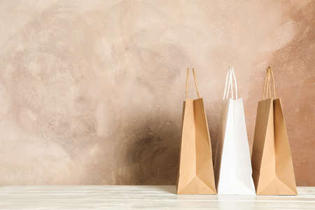 Paper bags on white table against brown background, copy space Stock fotó