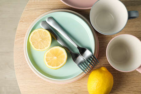 Plates and cups with lemons on wooden table, top view