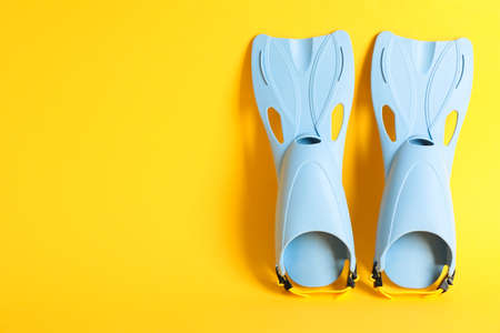 Pair of blue flippers on yellow background, space for text Imagens