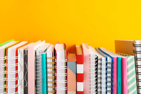 Stack of colorful books against background, space for text