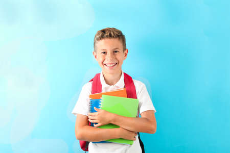 Boy with copybooks and backpack against color background, space for text