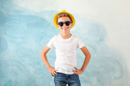 Boy with sunglasses and hat against color background, space for text