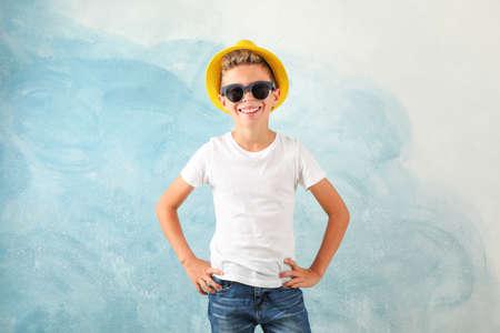 Junge mit Sonnenbrille und Hut vor farbigem Hintergrund, Platz für Text
