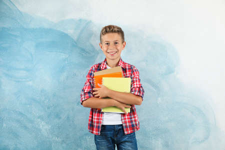 Boy with copybooks against color background, space for text