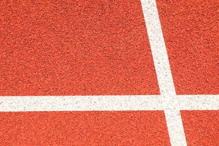 Rote Laufstrecke mit weißen Linien im Freien, Kopierraum