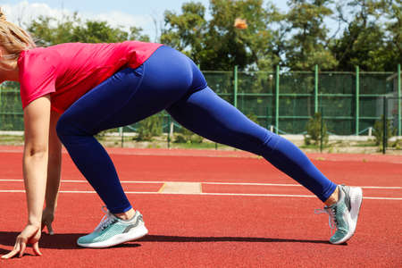 Girl low starting to run on red athletic track. Sport concept