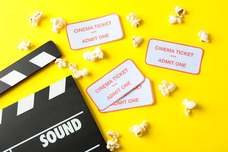 Flat lay composition with clapperboard, popcorn and tickets on yellow background Stockfoto