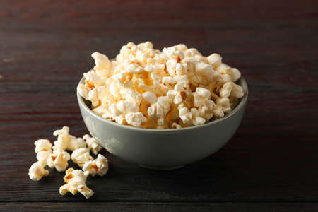 Bowl with popcorn on wooden background, space for text Standard-Bild