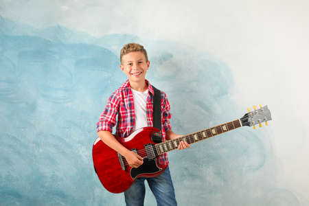 Happy boy with electric guitar on color background, space for text Stock Photo