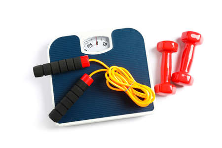 Weigh scales, skipping rope and dumbbells isolated on white background