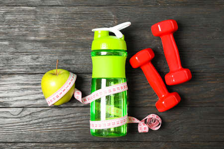 Bottle, measuring tape and apple on wooden background, copy space
