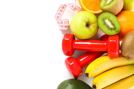 Dumbbells, measuring tape and fruits isolated on white background