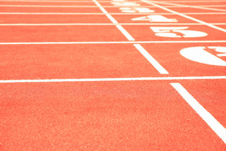 Start of red athletic track with numbers, space for text 写真素材