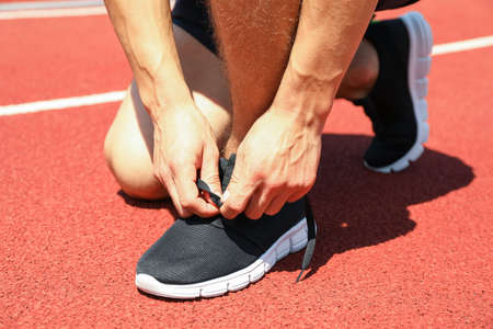 Man tying shoelaces on red athletic running track, close up 写真素材