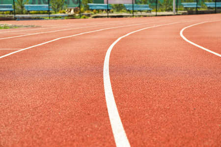 Red running track with white lines outdoor, copy space