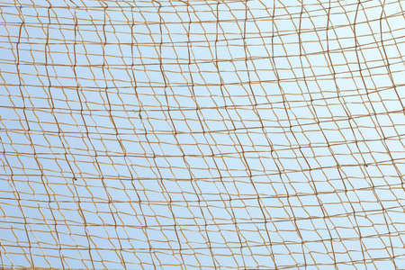 Football net against blue sky background, space for text