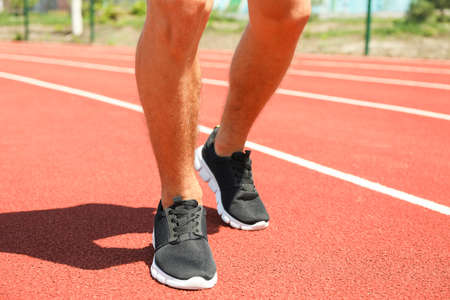 Man in sneakers on red athletic running track, close up
